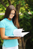 Portrait of attractive young woman with book in a green park Royalty Free Stock Photography