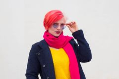 Portrait of an attractive young woman with colored hair and colorful clothes on a light background, glasses in the shape of hearts. Outdoor pink beauty multi royalty free stock image