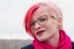 Portrait of an attractive young woman with colored hair and piercing under her lip. Glasses, piercings, multicolored hair.  royalty free stock images