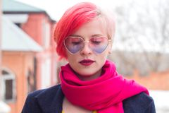 Portrait of an attractive young woman with colored hair and piercing under her lip. Glasses, piercings, multicolored hair.  royalty free stock image