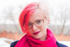 Portrait of an attractive young woman with colored hair and piercing under her lip. Glasses, piercings, multicolored hair. Outdoor pink winter smile beauty royalty free stock photo