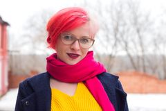 Portrait of an attractive young woman with colored hair and piercing under her lip. Glasses, piercings, multicolored hair royalty free stock photo
