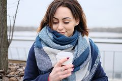Portrait of attractive young woman wearing scarf and holding white coffee cup on a cold and snowy winter day Stock Images