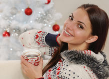 Portrait of an attractive young woman enjoying hot drink on Chri Stock Photos