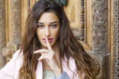 Portrait of attractive young woman with finger on lips. Portrait of attractive brunette woman with finger on lips, concept of student show quiet, silence, secret Stock Image