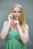 Portrait of attractive young woman with finger on lips. Portrait of attractive girl calling by phone with finger on lips. Concept of student show quiet, silence stock images
