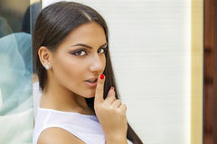 Portrait of attractive young woman with finger on lips Royalty Free Stock Photo