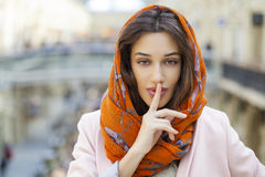 Portrait of attractive young woman with finger on lips. Portrait of attractive girl with finger on lips, concept of student show quiet, silence, secret gesture Royalty Free Stock Image