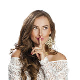 Portrait of attractive young woman with finger on lips. Portrait of attractive girl with finger on lips, isolated over white background concept of student show Royalty Free Stock Images