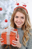 Portrait of an attractive young woman with a gift for Christmas Stock Image