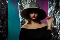 Portrait of attractive young woman in hat. With wide brim and red lips posing in studio on multiclor background Royalty Free Stock Image