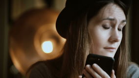Portrait of attractive young woman holding the smartphone and using wireless technology while visiting the cafe in city. Beautiful female browsing the Internet stock footage