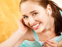 Portrait of attractive young woman listening to music at gym Royalty Free Stock Images