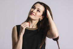 Portrait of an attractive young woman looking up and touching hair Stock Photography