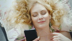 Portrait of an attractive young woman lying on a bed, uses a smartphone listening to music. View from above stock video footage