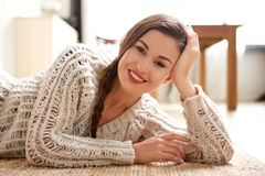 Attractive young woman lying on floor and smiling. Portrait of attractive young woman lying on floor and smiling Stock Photography