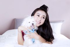 Attractive woman with Maltese dog on bed. Portrait of attractive young woman with Maltese dog, lying on the bedroom and smiling together Royalty Free Stock Photo
