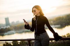 Attractive young woman with mobile phone outdoor. Portrait of attractive young woman with mobile phone outdoor Royalty Free Stock Photos