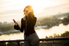 Attractive young woman with mobile phone outdoor. Portrait of attractive young woman with mobile phone outdoor Royalty Free Stock Photo