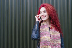 Portrait of attractive young woman with mobile phone in the stre Stock Images