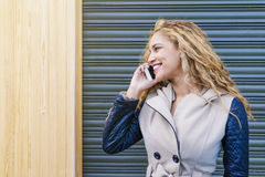 Portrait of attractive young woman with mobile phone in the stre Royalty Free Stock Photos