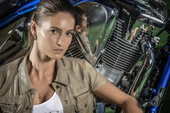 Portrait of attractive young woman, over motorcycle background Royalty Free Stock Photo