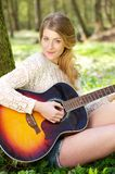 Portrait of an attractive young woman playing guitar outdoors Royalty Free Stock Images