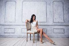 Portrait of attractive young woman sitting in a chair. elegant white dress. White floor and white wall in the background stock image