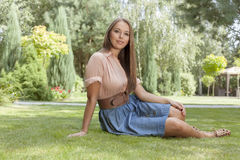 Portrait of attractive young woman sitting on grass in park Royalty Free Stock Image