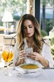 Attractive young woman sitting in restaurant and using mobile ph royalty free stock images