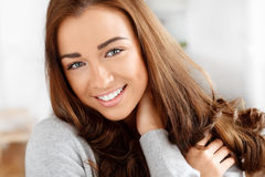 Portrait of an attractive young woman smiling. Attractive young woman smiling at home Stock Image
