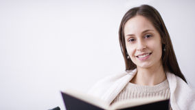 Portrait of an attractive young woman smiling to camera while reading a book Stock Photos