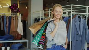 Portrait of attractive young woman standing with many paper bags in clothing store, smiling happily and looking at. Portrait of attractive young woman standing stock video footage