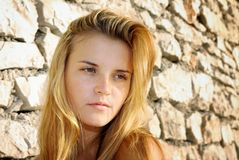Portrait of attractive young woman and stone wall Royalty Free Stock Image