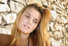 Portrait of attractive young woman and stone wall Stock Photography