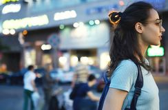 Portrait of attractive young woman on street with neon illumination, standing near copy space area for advertising. Side view of hipster girl in eyewear royalty free stock image