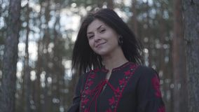 Portrait of attractive young woman tying the lace on a black and red dress standing under the trees in the pine forest stock footage