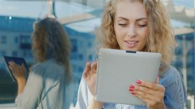 Portrait of an attractive young woman uses tablet. Near the urban mirror wall, positive emotions stock video footage