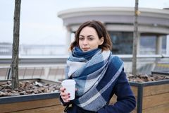 Portrait of attractive young woman wearing scarf and holding white coffee cup on a cold and snowy winter day Stock Photo