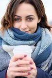 Portrait of attractive young woman wearing scarf and holding white coffee cup on a cold and snowy winter day Stock Photos