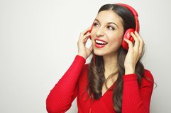 Portrait of an attractive young woman with white teeth red dressed listening to music with red headphones looking to the side on w royalty free stock photo