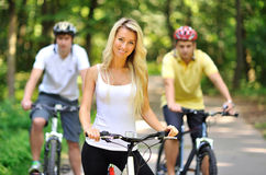 Portrait of attractive young woman on bicycle and two men behind Stock Photos