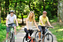 Portrait of attractive young woman on bicycle and two men in blu Stock Photos