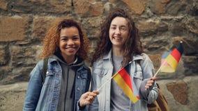 Portrait au ralenti des étudiants heureux dans de jolies filles de l'Allemagne ondulant les drapeaux allemands et riant regardant banque de vidéos