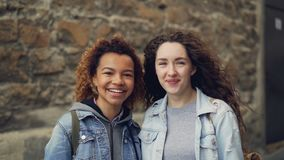 Portrait au ralenti en gros plan de deux étudiants heureux Afro-américain et appareil-photo de regard caucasien et rire mélangé banque de vidéos