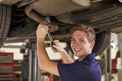 Portrait Of Auto Mechanic Working Underneath Car In Garage stock images