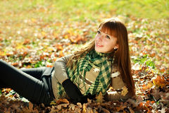 Portrait of autumn smiling girl lying on leaves Stock Images
