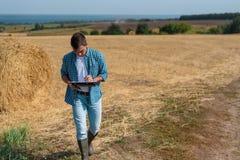 Portrait avant authentique d'agronome d'agriculteur de jeune homme dans la meule de foin photographie stock
