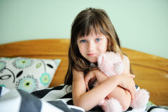 Portrait of awaken little girl sitting in bed Royalty Free Stock Images