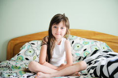 Portrait of awaken little girl sitting in bed Royalty Free Stock Photos